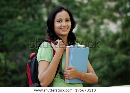 Happy young female student at college campus and carrying books