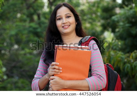 Happy young female student at outdoors - stock photo