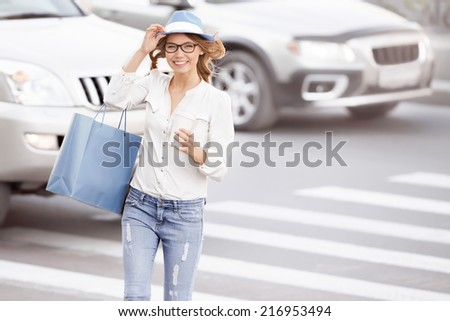 Happy young female student crossing the street with a coffee-to-go cup and tipping hat against urban city background. - stock photo