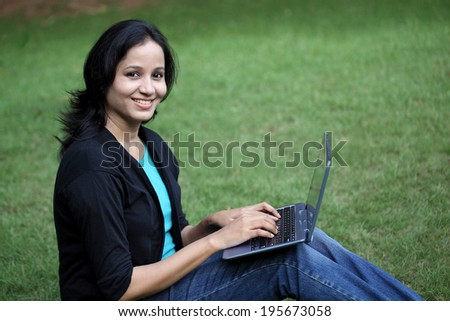 Happy young female student working with tablet computer at campus