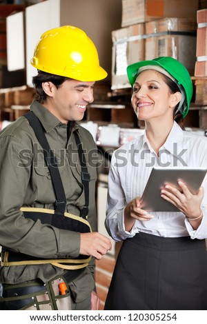 Happy young female supervisor with digital tablet and foreman at warehouse - stock photo