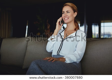 Happy young female talking on mobile phone while enjoying rest in modern interior after hard work day,successful businesswoman having nice conversation with boss via cell telephone before presentation - stock photo