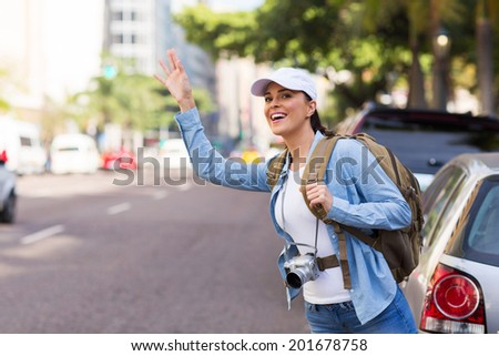happy young female tourist hailing for a cab in the city - stock photo