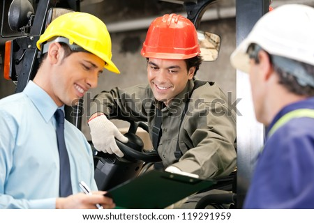 Happy young forklift driver with supervisor holding clipboard at warehouse
