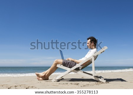 Happy young freelancer working online with laptop on a sunny tropical beach