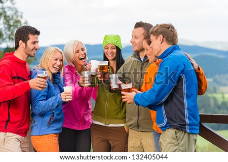 Happy young friends clinking glasses and drinking beer outdoors - stock photo