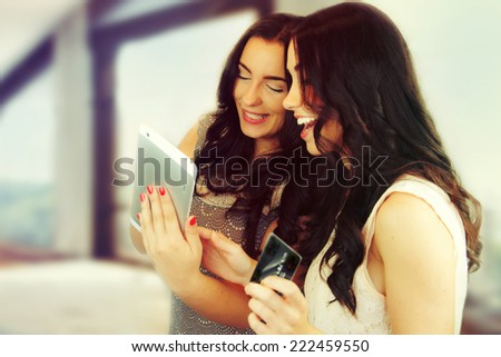 Happy young friends doing shopping on internet.