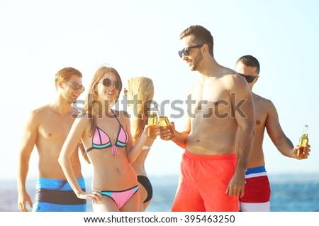 Happy young friends drinking beer at the beach, on sky background - stock photo