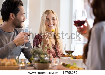 Happy young friends enjoying lunch at a restaurant. Woman eating baked potatoes while friends drinking red wine. Happy smiling friends having dinner at home.