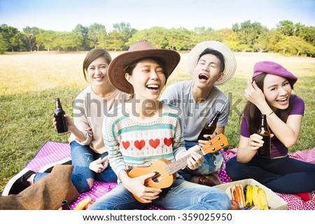 happy young friends enjoying picnic and playing ukulele  - stock photo