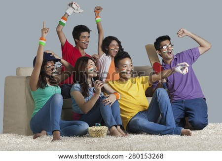 Happy young friends having a great time together while watching cricket match at home - stock photo