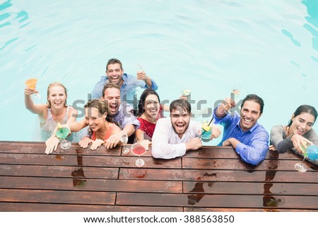 Happy young friends having drinks at swimming pool enjoying holiday - stock photo