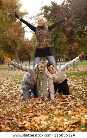 Happy young friends having fun in autumn park, girl kneeling on boys back. - stock photo