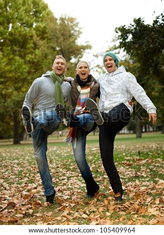Happy young friends having fun in park, laughing. - stock photo