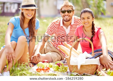 Happy young friends having picnic in the country - stock photo
