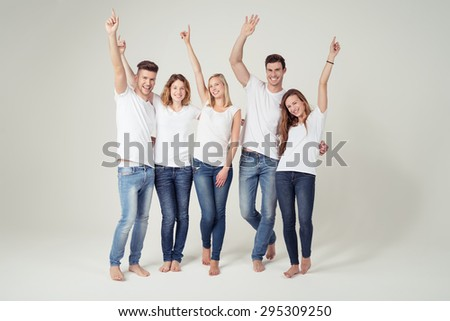 Happy Young Friends in Casual White Shirt with Copy Space and Blue Jeans, Raising their Arms and Smiling at the Camera on White Background. - stock photo