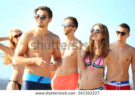Happy young friends relaxing at the beach, outdoors