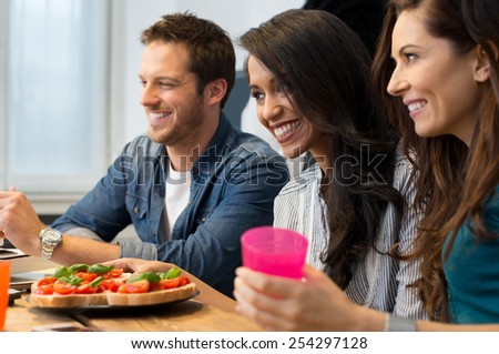 Happy young friends sitting beside bruschetta served on table - stock photo
