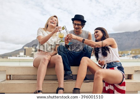 Happy young friends sitting on steps and toasting cocktails. Young people having a rooftop party. Man and woman hanging out outdoors sitting together. - stock photo
