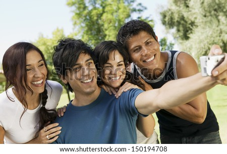 Happy young friends taking self portrait with digital camera at park