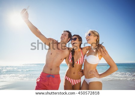 Happy young friends taking selfie with mobile phone on beach