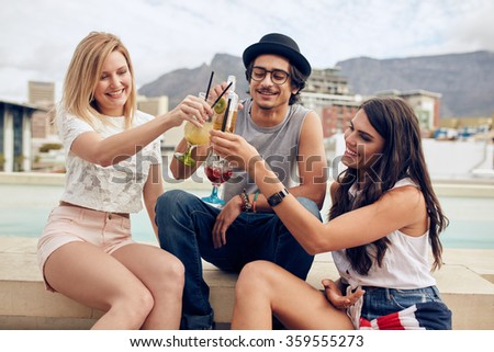Happy young friends toasting cocktails at a rooftop party. Young people hanging out and enjoying drinks.
