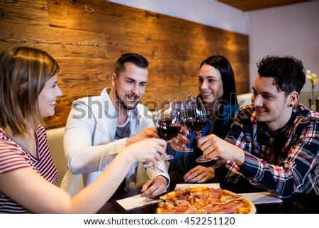 Happy young friends toasting wine at table in bar