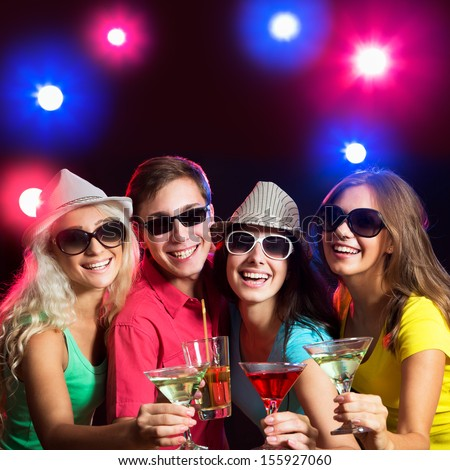 Happy young friends touching the glasses with each other at party - stock photo