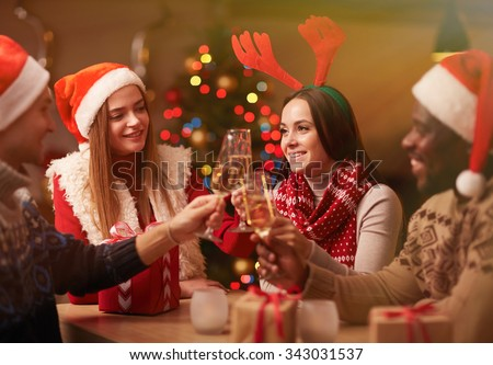 Happy young friends with champagne celebrating Christmas