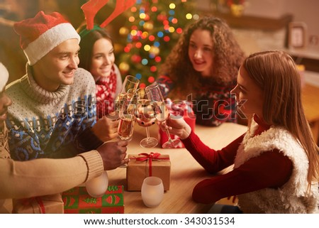 Happy young friends with flutes of champagne toasting on Christmas home party - stock photo