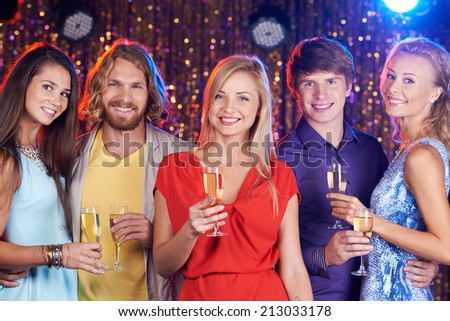 Happy young friends with flutes with champagne looking at camera - stock photo