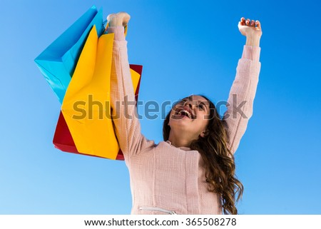 Happy young girl after shopping in a sunny day - stock photo