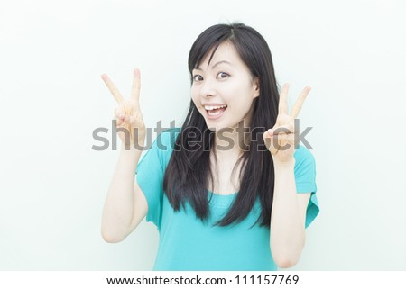 happy young girl cheering against pale green background