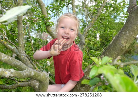 Happy young girl climbing in a tre - stock photo
