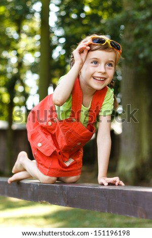 Happy young girl crawl on all fours on the beam in the park