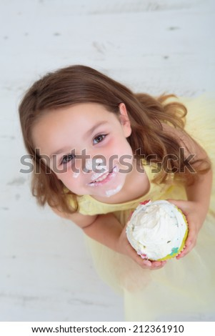 Happy young girl eating cream cake - stock photo