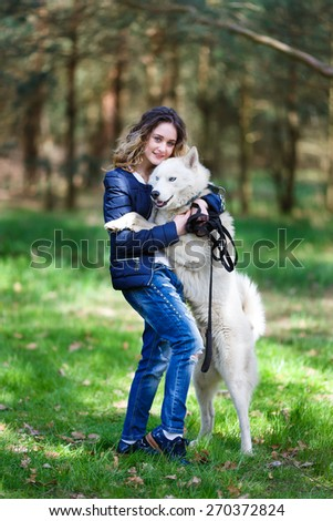 Happy young girl embracing husky dog in a forest at spring time