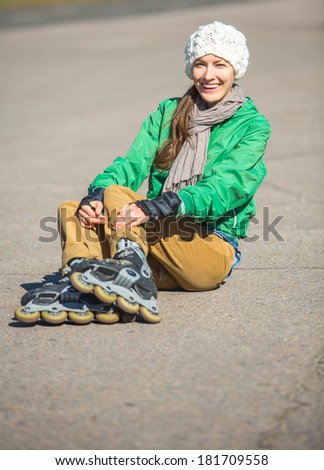 Happy young girl enjoy roller skating rollerbalding on inline skates in park. Woman in outdoor activities - stock photo