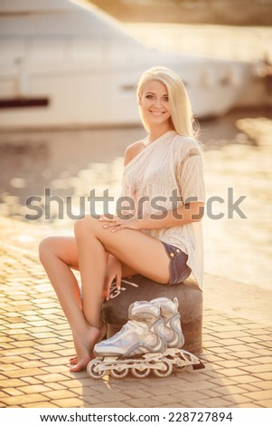 Happy young girl enjoying roller skating rollerblading on inline skates sport in park. Woman in outdoor activities. Beautiful teenage girl rollerskating in park - stock photo