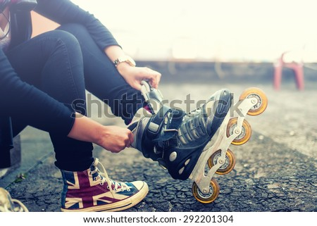 Happy young girl enjoying roller skating, rollerblading, putting on rollerskates after activities. Vintage effect on photo - stock photo