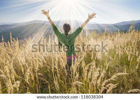 Happy young girl enjoying the beauty of sunny autumn day high in the mountains - stock photo