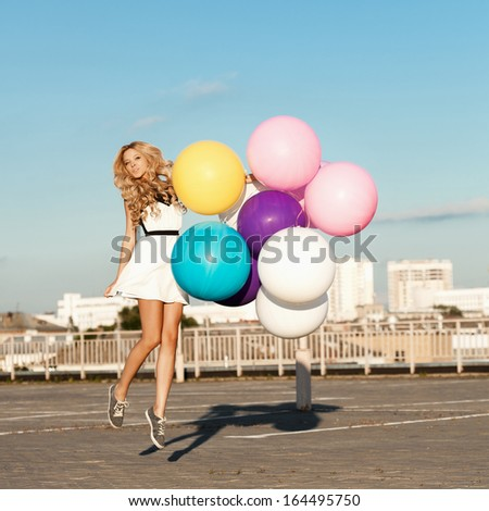 Happy young girl flying with big colorful latex balloons.  Gorgeous thick wavy hair. Outdoors, lifestyle - stock photo