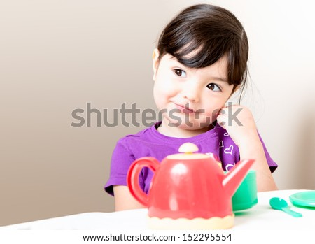 Happy young girl gets an idea as she drinks her tea - stock photo