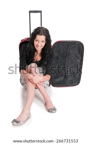 Happy young girl going on vacations , sitting on suitcase