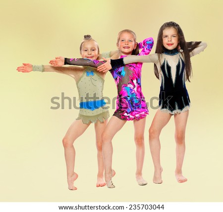 happy young girl gymnast standing in a row in the direction of putting your hands.