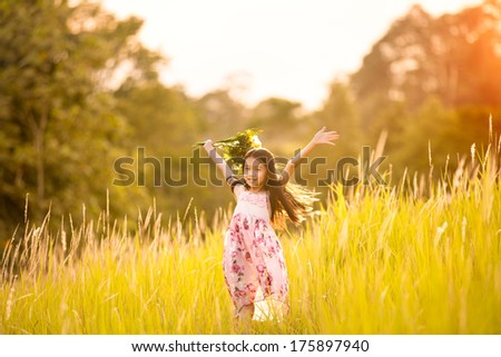 Happy young girl holding flowers and standing on countryside meadow with raised hands - stock photo