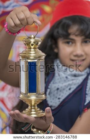 Happy Young Girl Holding Lantern Celebrating Ramadan over Ramadan Fabric - stock photo