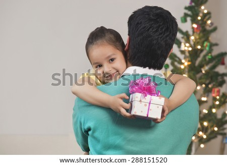 Happy young girl hugs her dad while holding Christmas gift - stock photo