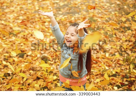 Happy young girl in autumn park