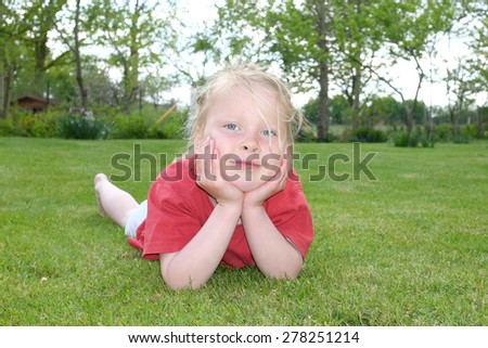 Happy young girl in the garden lying in grass - stock photo